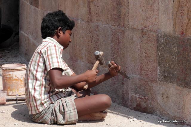 Enfant nettoyeur de joints de pierres